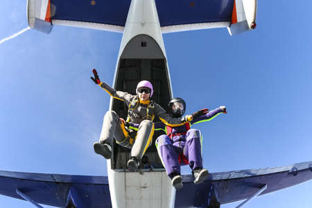 Two girls skydivers jump out of an airplane