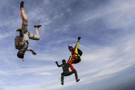 parachutists: Three parachutists perform freestyle figures in free fall. Stock Photo