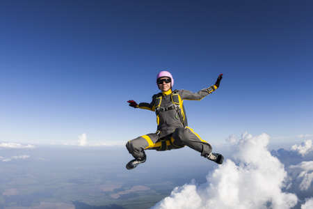 parachuting: The girl parachutist performs figure freestyle in freefall.