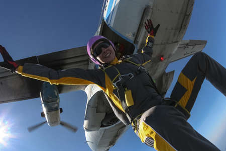 parachuting: The girl parachutist jumps out of an airplane and fly freestyle