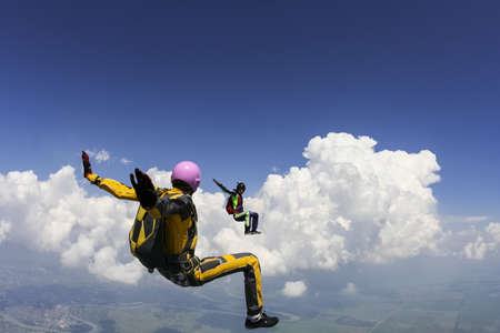 parachutists: Two girls parachutists perform freestyle figures in free fall  Stock Photo