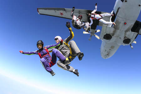 parachute jump: A group of paratroopers jumping out of an airplane