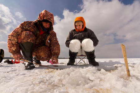 ice fishing: Father and daughter fishing on the ice-fishing