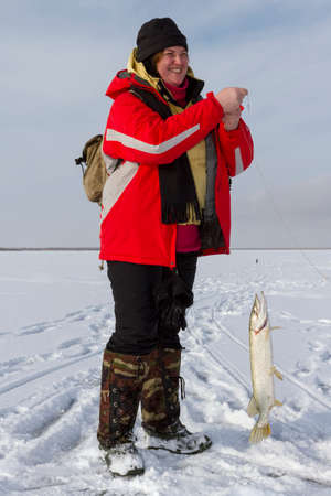 ice fishing: Woman caught fish on ice fishing. Stock Photo