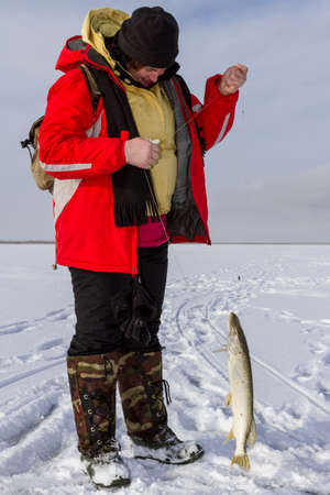 Woman caught fish on ice fishing. photo