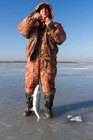 ice fishing: The man caught the fish on ice fishing.