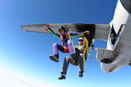 Two girls skydivers jump out of an airplane. Standard-Bild