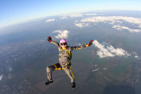 parachuting: The girl parachutist performs figure freestyle in freefall  Stock Photo