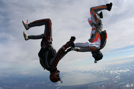parachutists: Two parachutists perform fall hand in hand upside down  Stock Photo