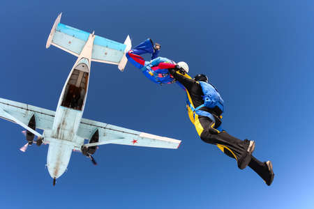 parachutists: Two parachutists jumping out of an airplane in the bunch