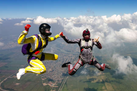 A girl and a guy skydivers perform pieces in free fall