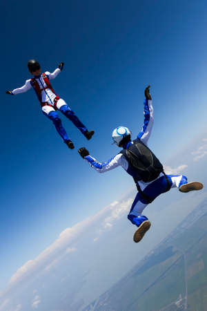 jumpsuit: A girl and a guy skydivers perform pieces in free fall. Stock Photo