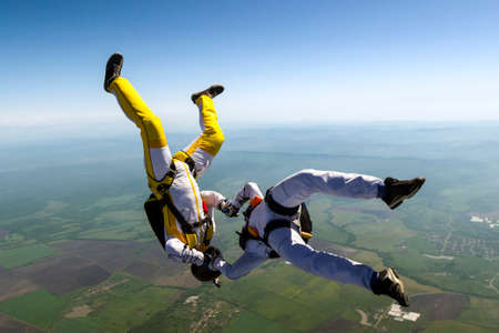 freefall: Two skydiver in freefall in the clouds