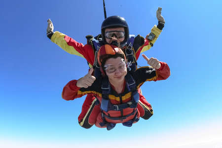 Tandem jump. The girl with the instructor in freefall. Stock Photo