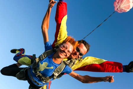 Tandem jump  The girl with the instructor in freefall  스톡 콘텐츠