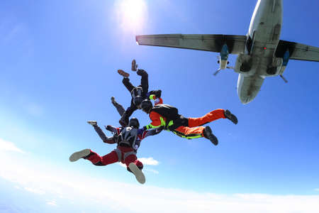 parachute jump: Four parachutists jumping out of an airplane