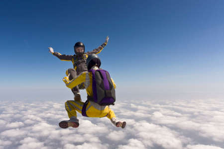 parachutists: Two parachutists girls in free fall in the clouds. Stock Photo