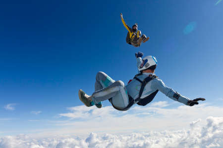 Girl and guy skydivers in freefall in the clouds