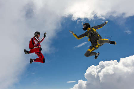 parachutists: Two parachutists girls in free fall in the clouds