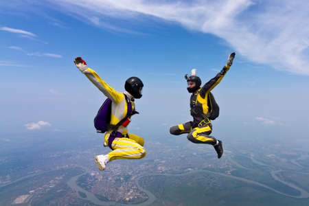 parachutists: Two girls parachutists in free style. Stock Photo