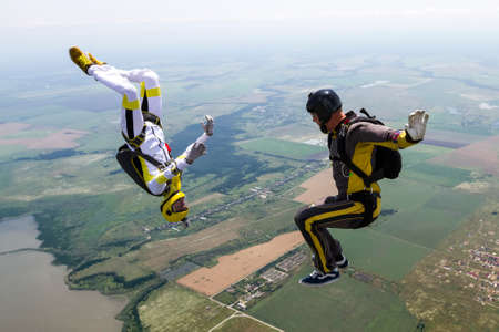 extreme danger: A girl and a guy skydivers perform pieces in free fall. Stock Photo