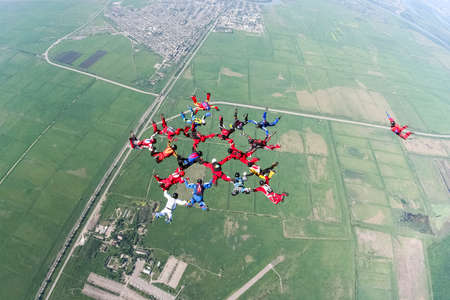 A group of paratroopers construct figures in free fall. Reklamní fotografie