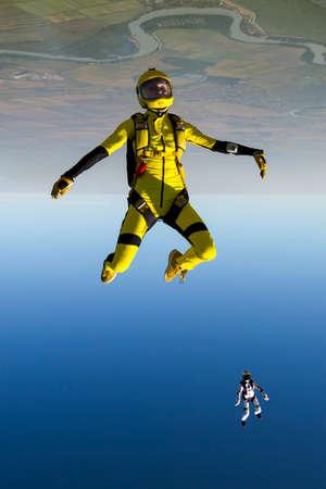caida libre: El paracaidista de la muchacha realiza cifra estilo libre en ca�da libre.