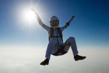 freefall: The girl parachutist performs figure freestyle in freefall.