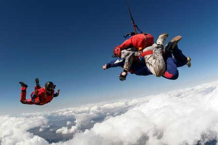 parachuting: Skydiver videographer shoots tandem jump. Stock Photo