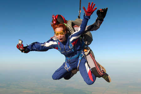 Tandem jump. The girl with the instructor in freefall. Standard-Bild