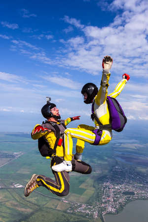 extreme sports: A girl and a guy skydivers perform pieces in free fall. Stock Photo
