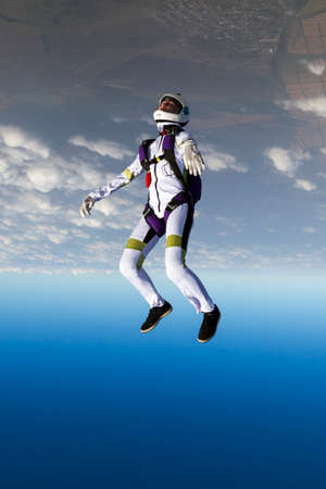 jumpsuit: The girl parachutist performs figure freestyle in freefall.