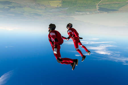 Two sports parachutist build a figure in free fall. Extreme sport concept. Stock Photo