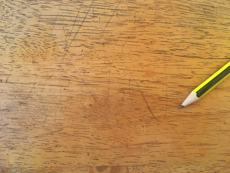 Green and yellow pencil on bright wood floor