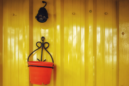 The walls are made of zinc, painted in yellow, the lamp is black, the flower pot is orange.