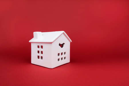 White porcelain house on red background