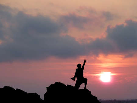 silhouette of a man at the top of the mountain against the sky photo