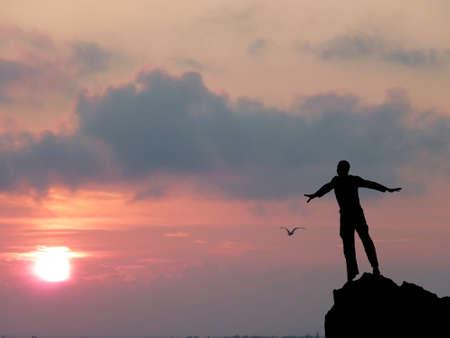 하늘에 대한 산 꼭대기에서 한 남자의 실루엣