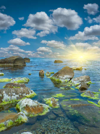 spring tide: stones into the sea on sunny sky background Stock Photo
