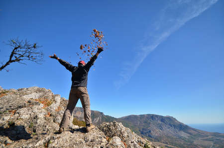 man on the mountain throws a bunch of autumn leaves photo