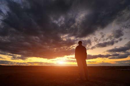 lejos: Silueta del hombre en la puesta del sol. Escena emotiva. Foto de archivo