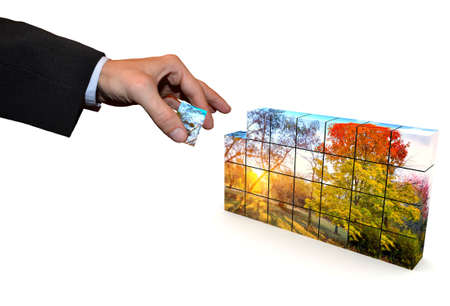 autumn park picture composed of a mosaic cubes, one part of which is in the hand of man in a suit