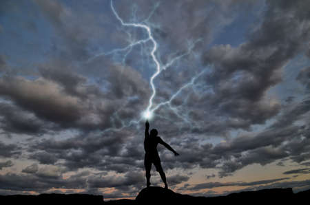 thunder storm: silhouette of a man on the hill out of the hand produces lightning. natural composition Stock Photo