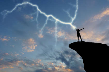 electrocute: silhouette of a man on a mountain top manufactures of hand zipper. natural composition