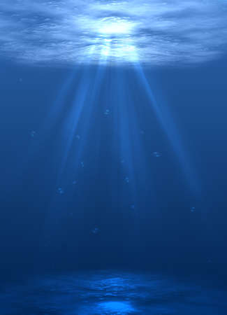underwater diving: the ocean floor with bubbles of air and bright sunlight