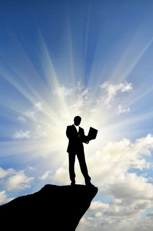 silhouette of a businessman with a laptop in hand is on top of a mountain in the sky with clouds. photo