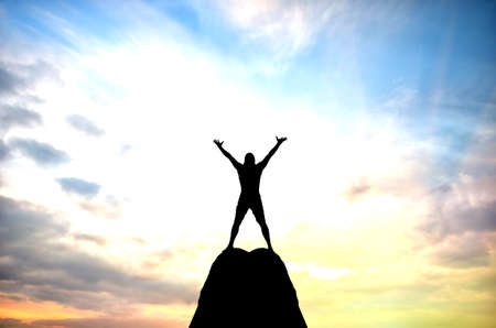 victory stand: man on top of the mountain reaches for the sun