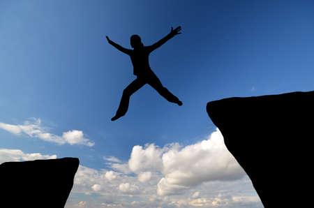 하늘에 또 다른 하나의 바위에서 점프 여성의 실루엣