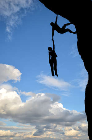 man on a rock holding the hand of a woman dangling over the precipice in the sky photo