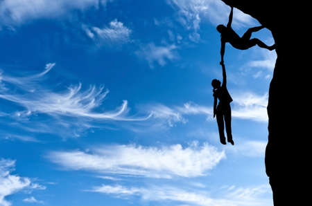 man on a rock holding the hand of a woman dangling over the precipice in the sky Stockfoto